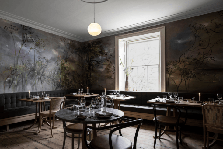 French artist Claire Basler, known for her botanical-themed works, created the moody mural in the dining room.