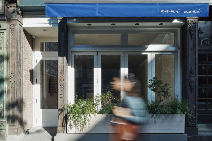 The front of the restaurant, on Carmine Street, has a blue awning that reflects the casual beachy sensibility of the interiors.