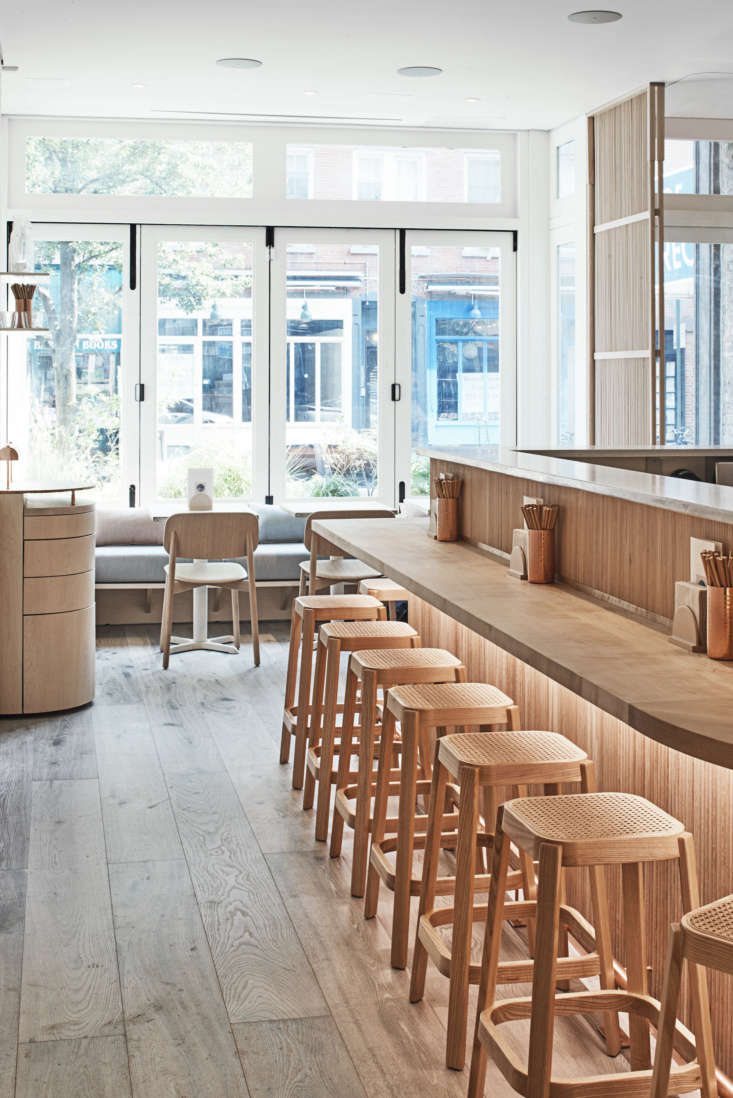 Wall-to-wall storefront windows allow for ample natural light. The restaurant seats 40, many of them on these rattan stools.