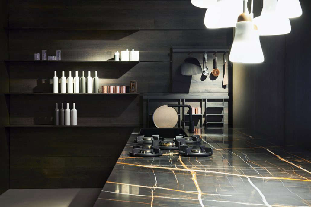 A kitchen by Key Cucine with a a black marble countertop and inset burners from Pitt.