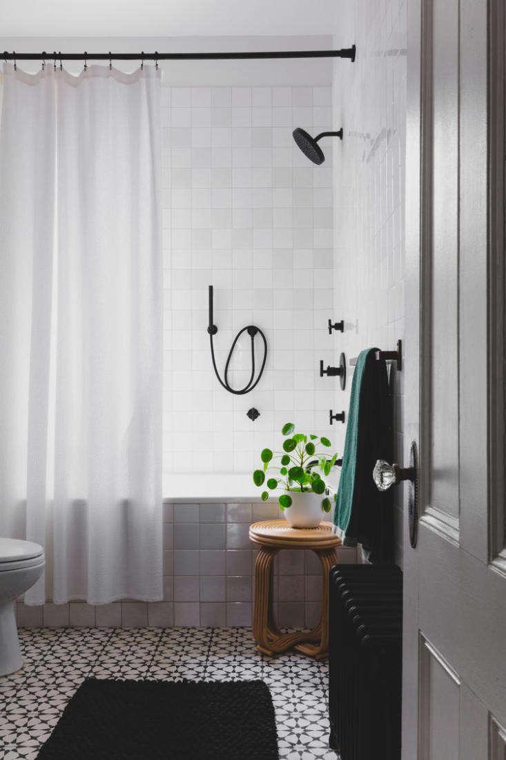 Like the entry, the bathroom has a black-and-white floor of Agadir Cement Tile: &#8