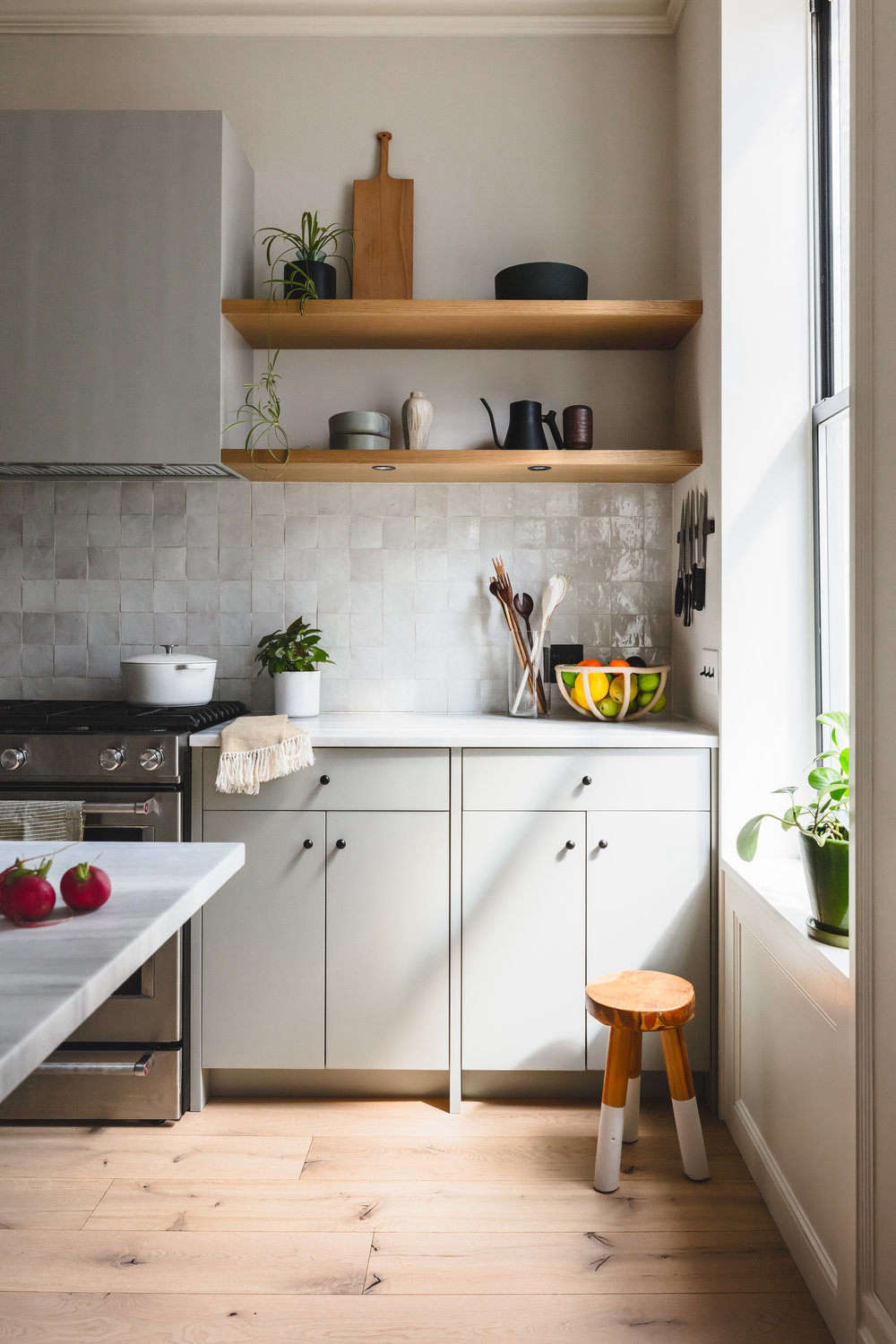 The counter and open shelves are reserved for a few kitchen tools, such as cutting boards and wooden spoons by Allison Samuels of Two Trees Studio and a Terracotta Fruit Bowl by Virginia Sins. Dishes and the couples&#8
