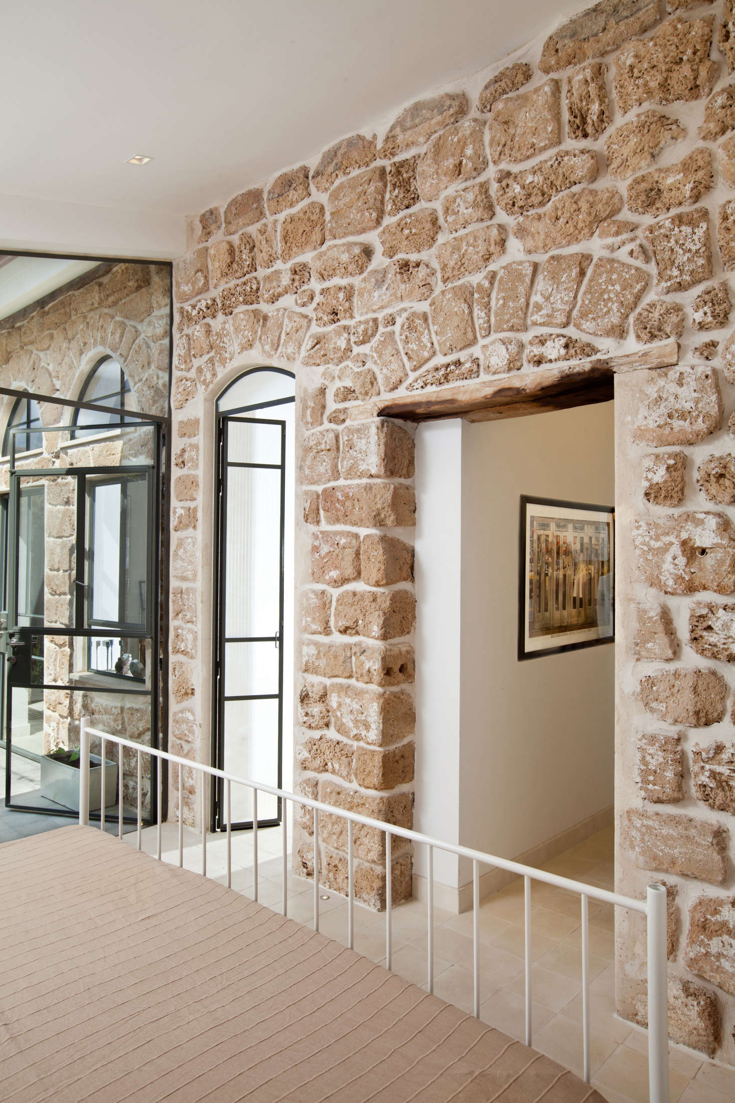 To contrast with the original limestone wall and maintain a feeling of openness, Dvir and Canetti added walls and doors made of glass and steel, like these in the guest bedroom.