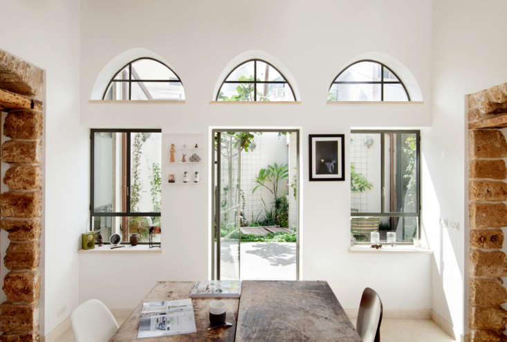The house is petite—only00 square feet—and square-shaped, with one corner cut off, all surrounding the original courtyard filled with fig trees and cyclamens, the architects say.