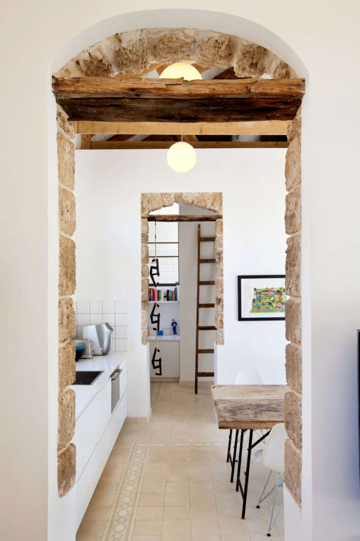 Twin archways lined with original stone lead into the simple white kitchen.