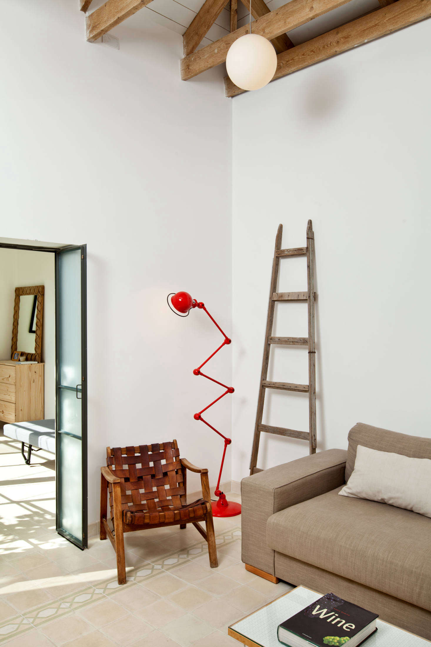 A red standing lamp adds an unexpected jolt of color to the otherwise-neutral sitting area. The lighting throughout is from Israeli company Dori Kimhi.