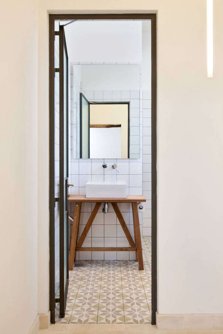 The master bath is fitted with painted tiles from Gluska and a steel-frame door.