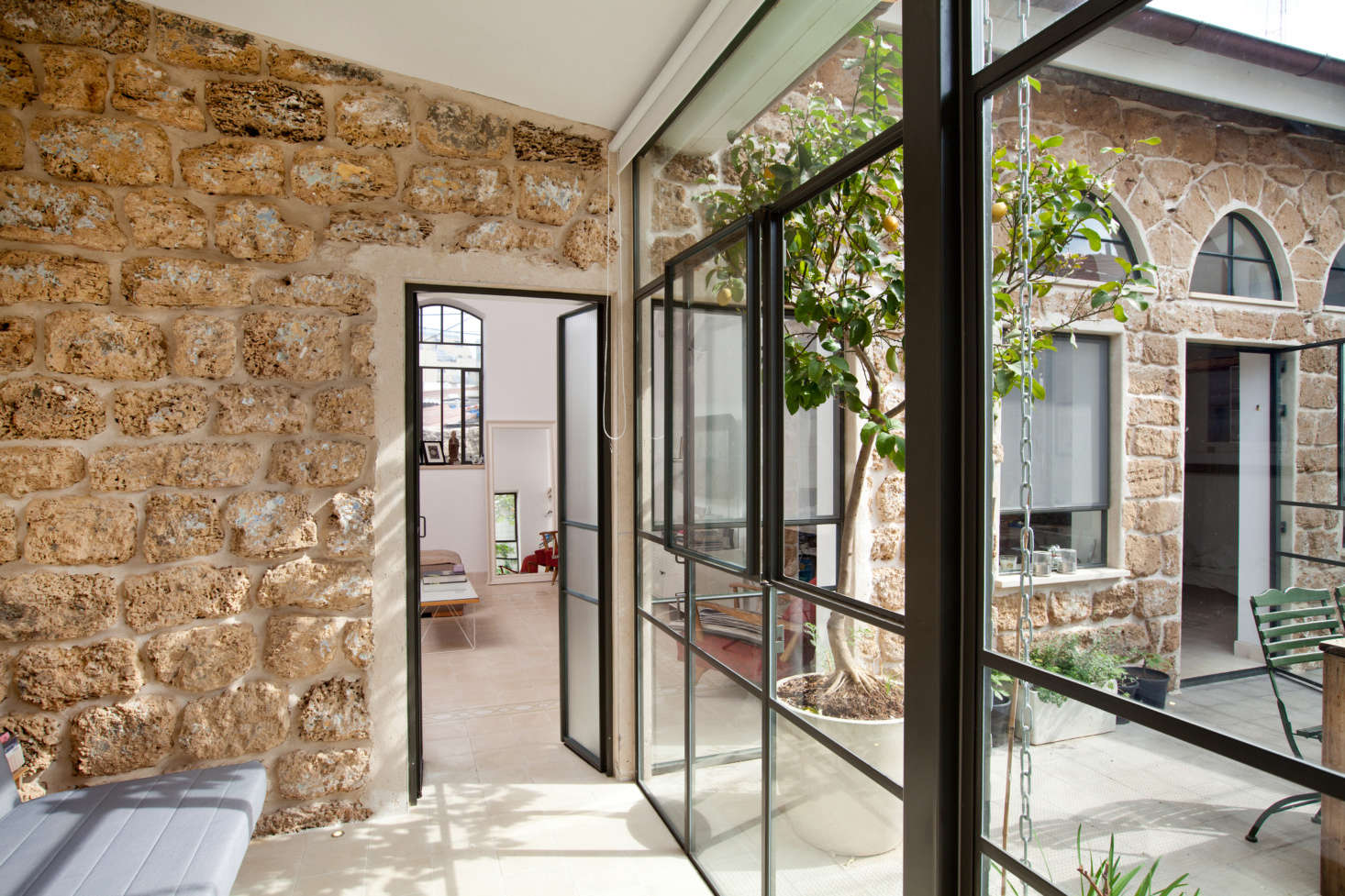 Another glass and steel wall makes the interiors feel like an extension of the courtyard..