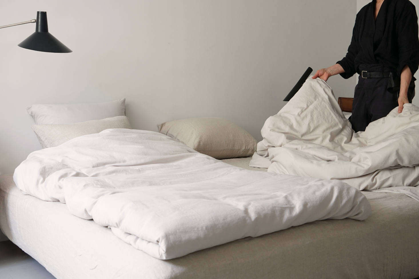 Think burrito-style: fold in the sides of each comforter and flip the bottom up, then turn over. Position side by side, so each duvet has equal real estate.