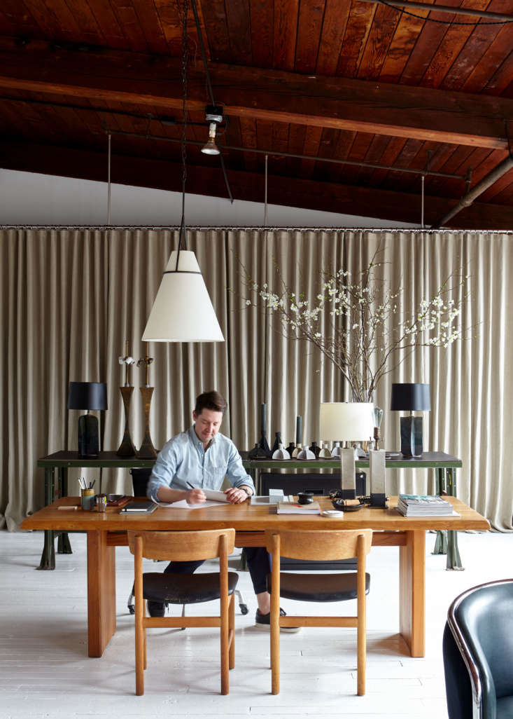 Kevin works from a 60s French desk/dining table designed by Pierro Chapo. The pendant light with a paper shade and bronze frame is Kevin&#8