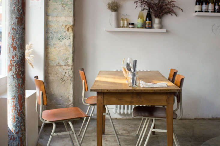 A simple table, with school chairs, a glass jar to hold cutlery, and dried grasses.