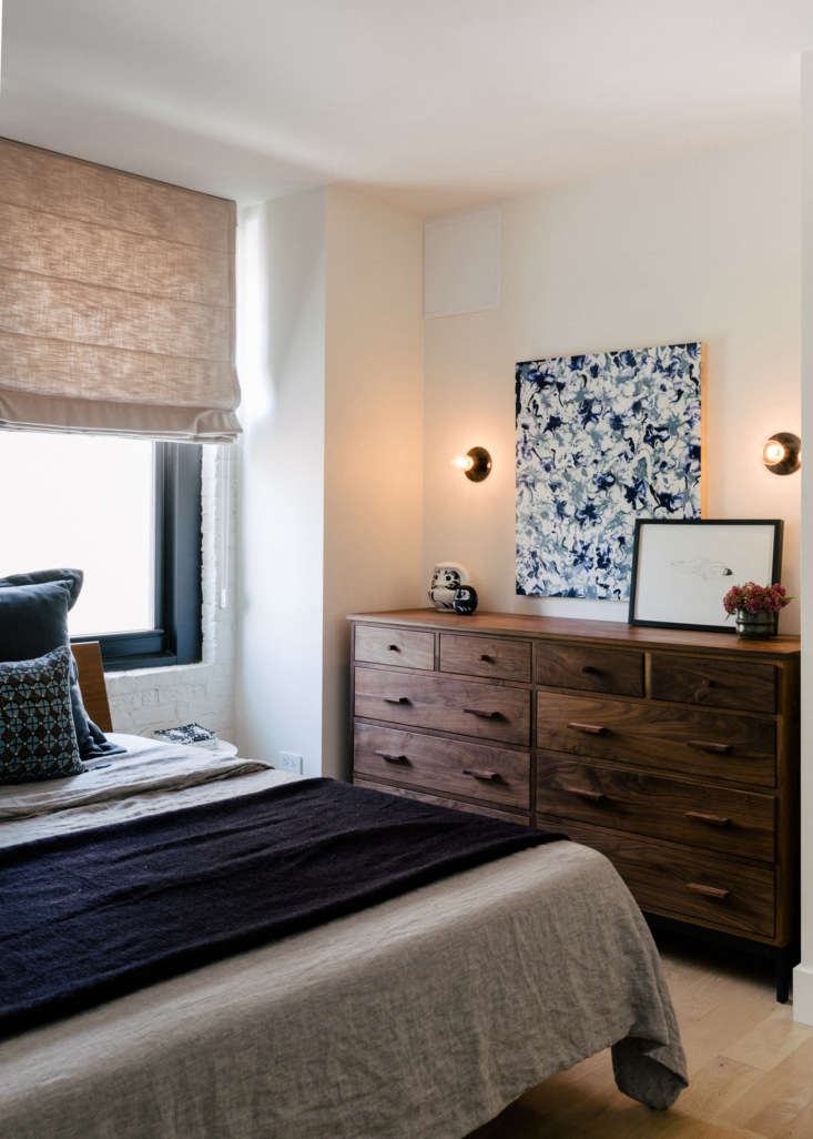 a bedroom features exposed brick walls, painted white, and layered linen beddin 18