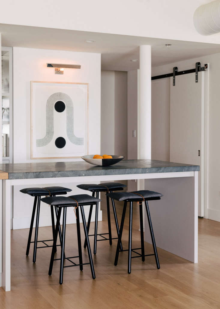 the counter extends into an eating and mingling space topped with gray green so 15
