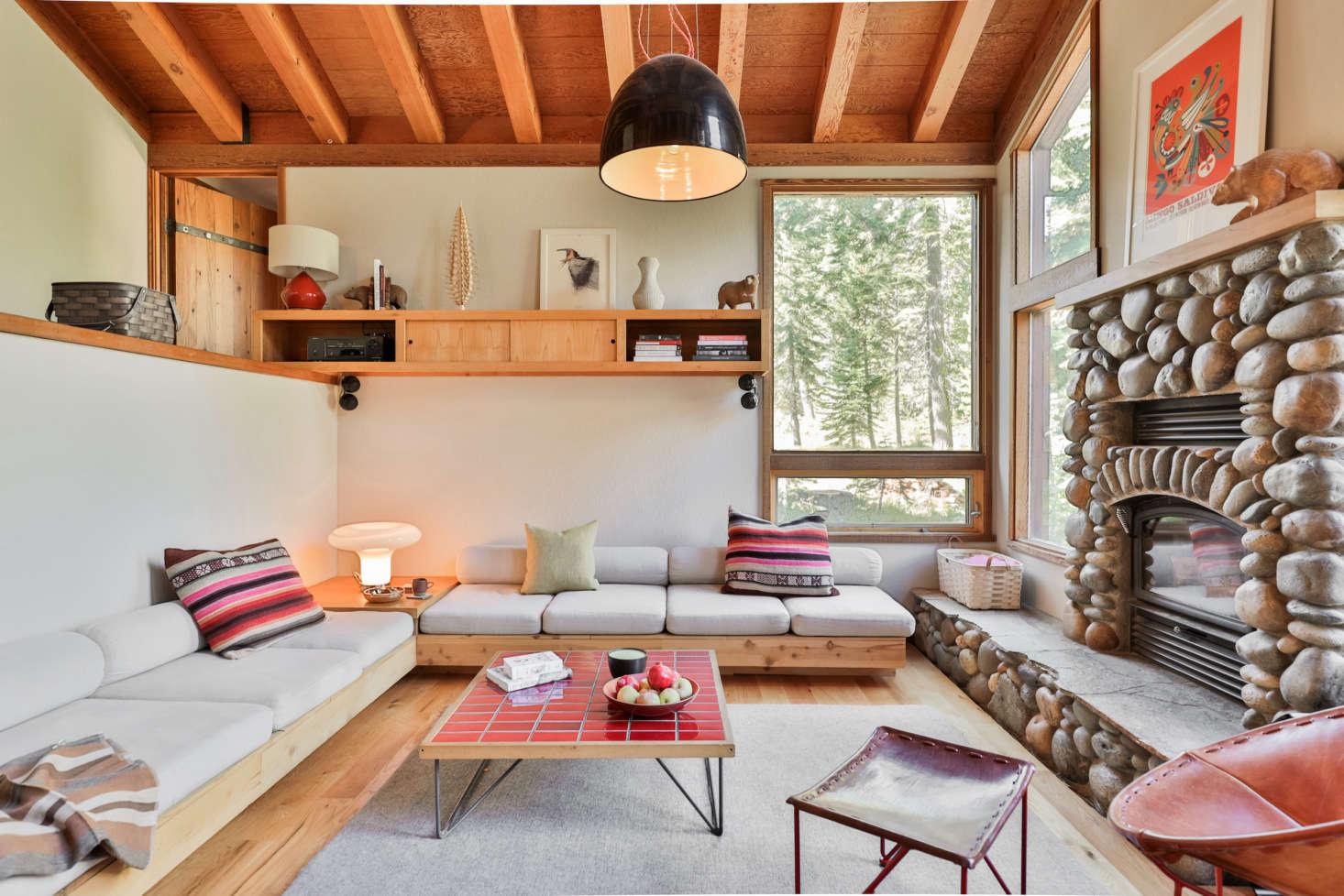 The living room features low-slung seating for gathering around the stone fireplace.