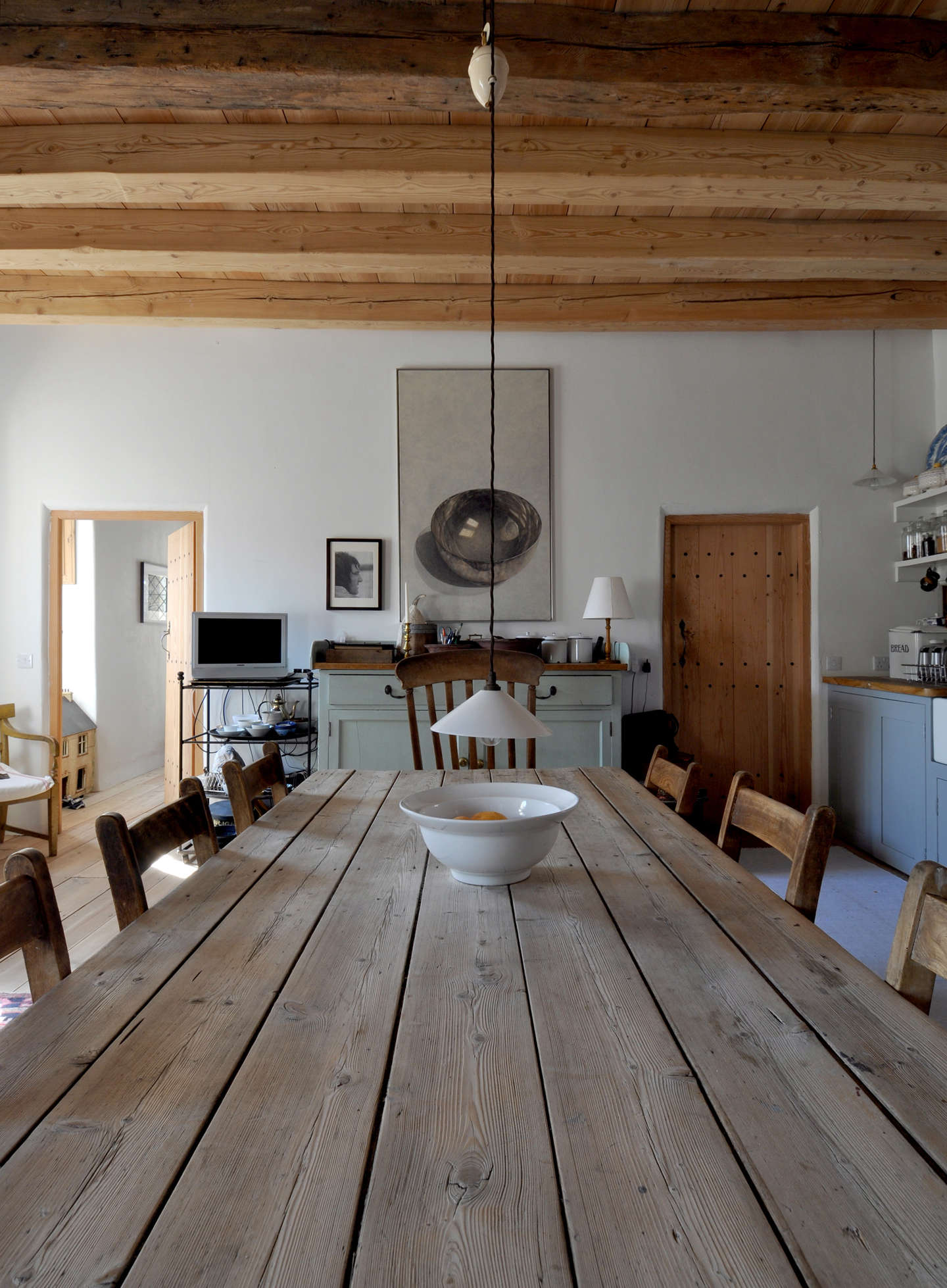 The antique dining table was originally used in the ironing room of a laundry facility.