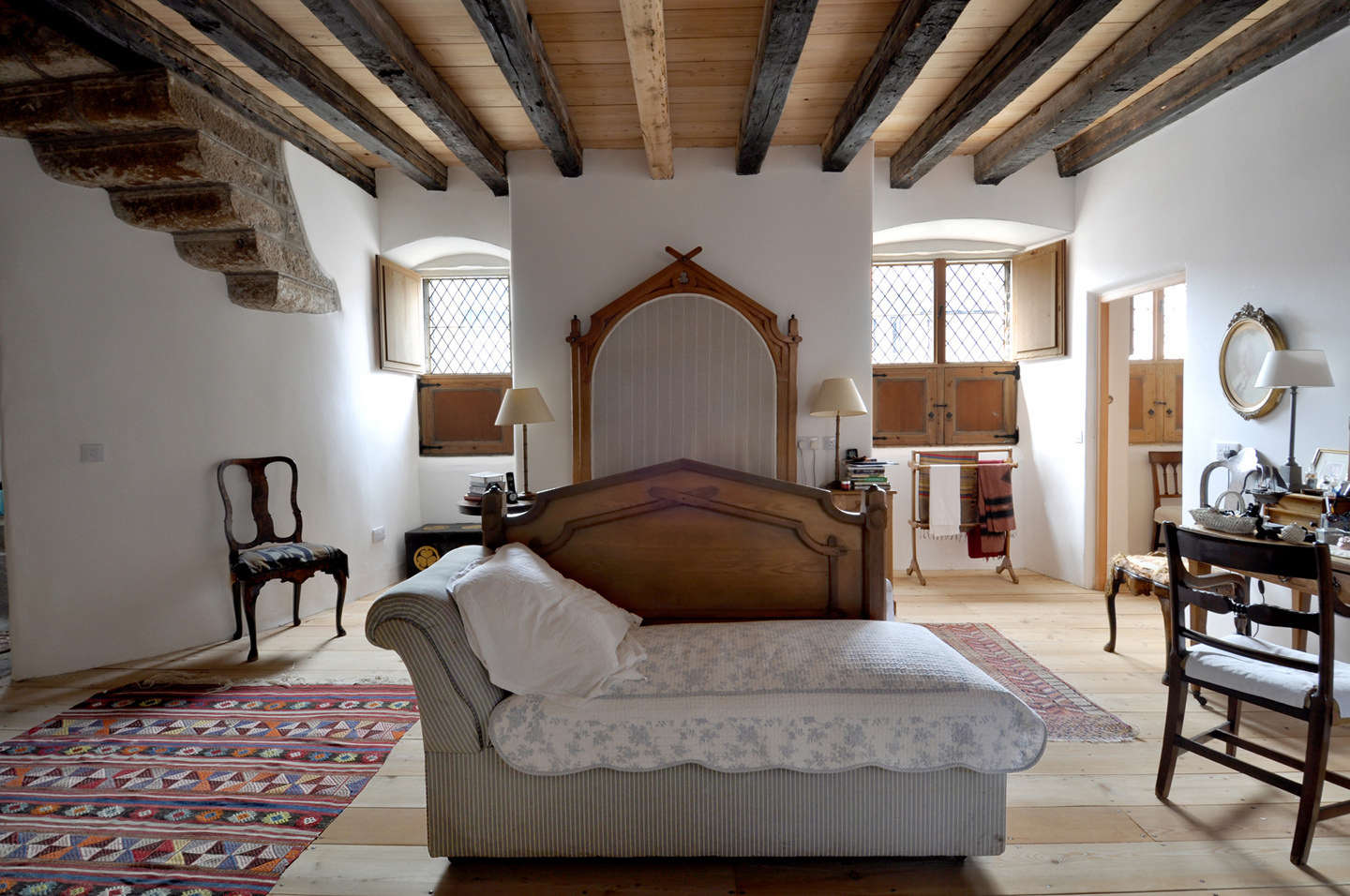 The main bedroom features an antique bed and colorful kilims.