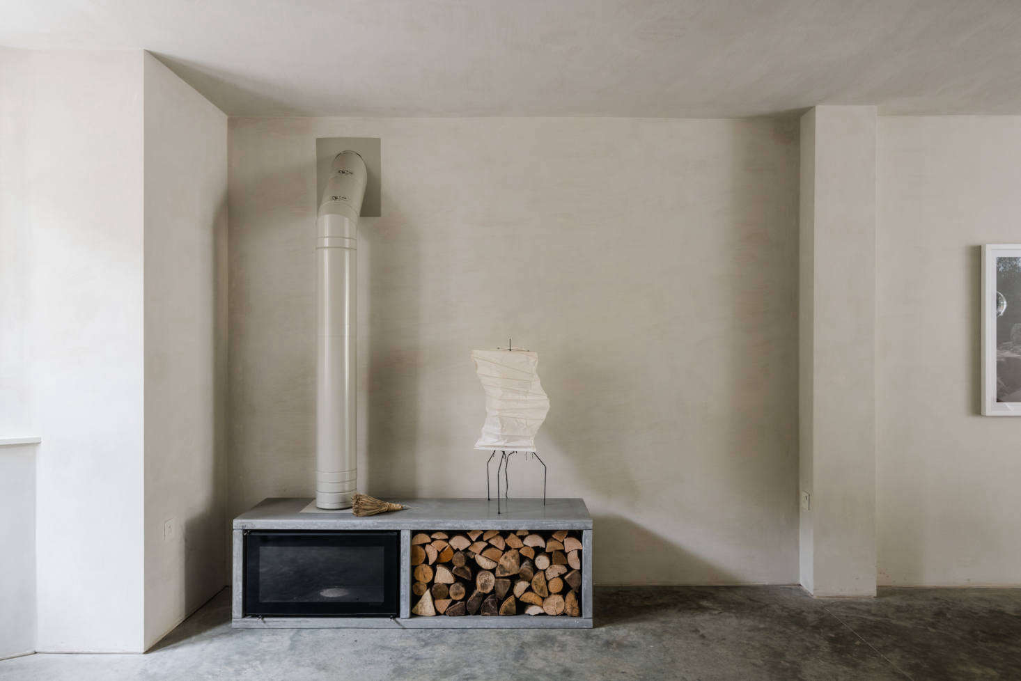 A Noguchi lamp sits atop a Stovax wood-burning stove set in a custom polished-concrete surround. (See src=