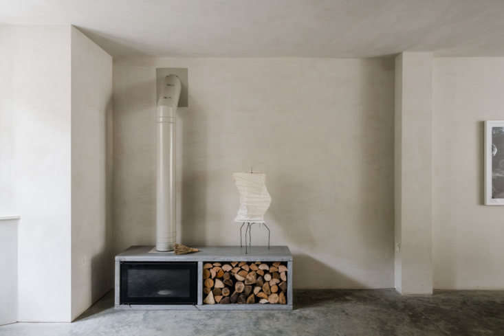 A Noguchi lamp sits atop a Stovax wood-burning stove set in a custom polished-concrete surround. (See loading=