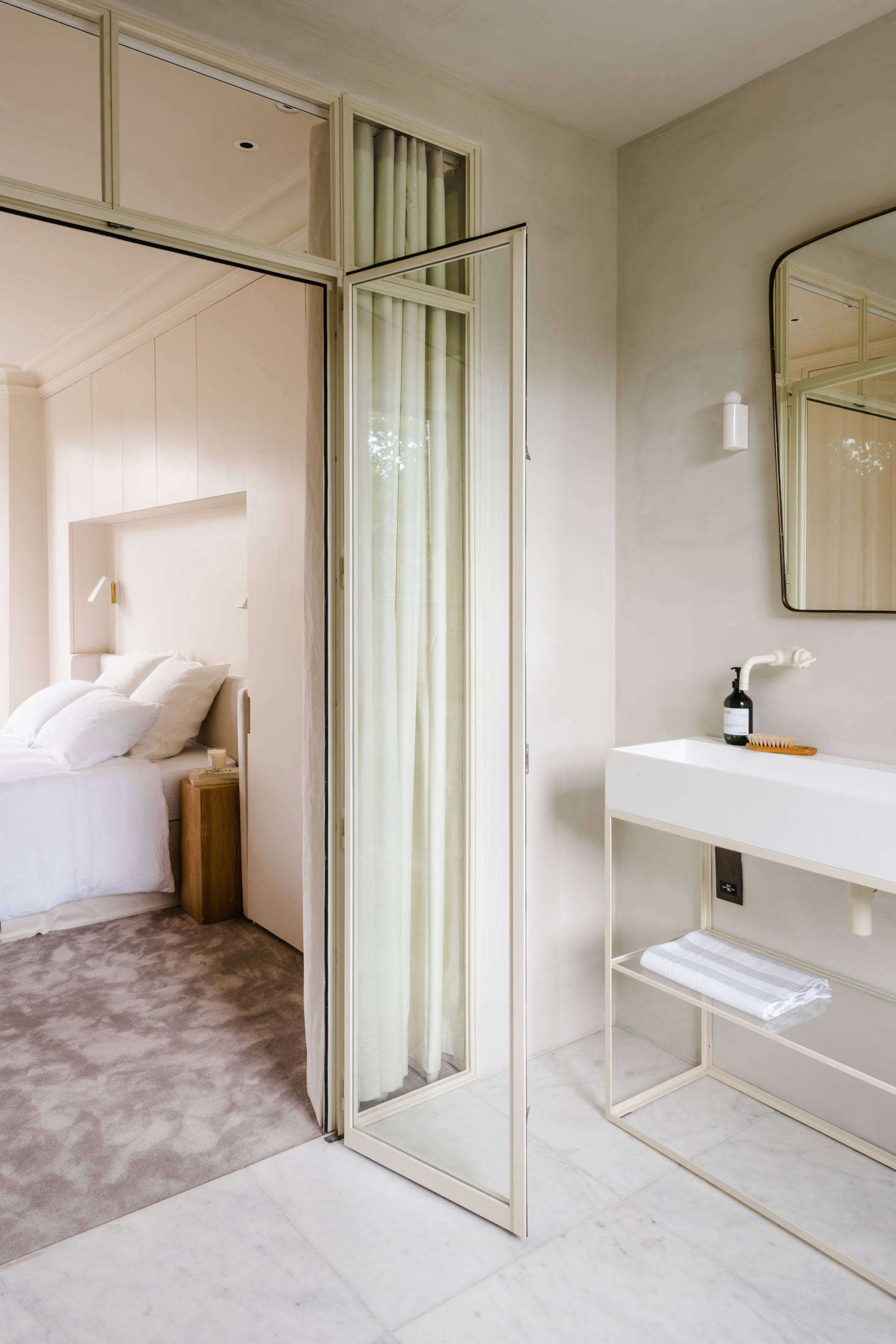 A steel and glass partition separates the bedroom from the bath. The custom vanity unit is from Iusso Stone.