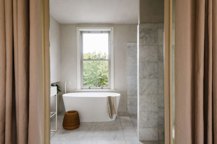 Large Calacatta marble tiles on both the floor and the walls.