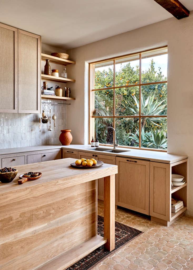 Dish washing with a view: the wood-framed window overlooks a lush garden and mandarin tree. The counters are Topus Concrete by Caesarstone. For nuance and depth, the walls are finished with limewash paint from Bauwerk Colourof Germany. Note the contrasting graining on the cabinets and island.
