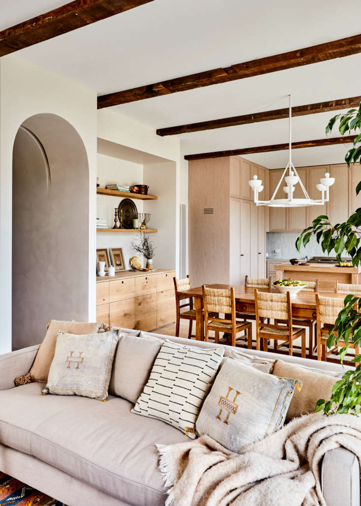 Many walls were removed over the course of this remodel: the kitchen is wide open to the living-dining area. Georgia designed the plasterwork light over the table—she has a line of plaster lights coming next year. The archway is one of several she introduced to the house: &#8