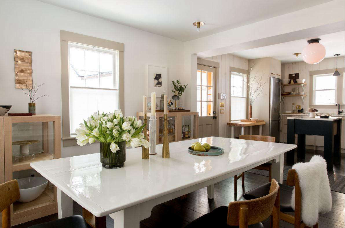 The dining area is now open to the kitchen. It has a farmhouse table newly painted a high-gloss white. The walls throughout are Benjamin Moore White Heron and the windows are original. The couple bought their pair of Piet Boon display cabinets on Chairish. Photograph by Allegra Anderson.