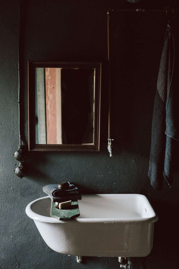 A dark-hued bath, with perfectly off-center mirror, in the Schoolhouse.