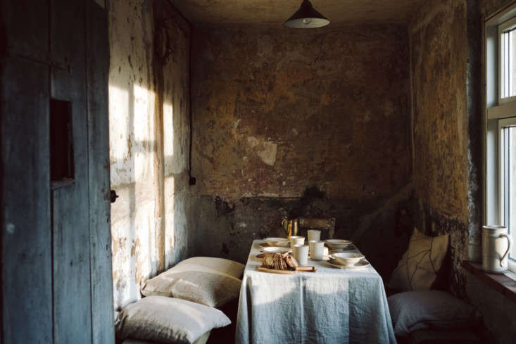 Exposed, stripped-back walls stand in lieu of wallpaper or paint. Here, a dining nook, with linen cushions and winter light. Christina and Knut also offer meals, prepared in their farmhouse kitchen, for groups.