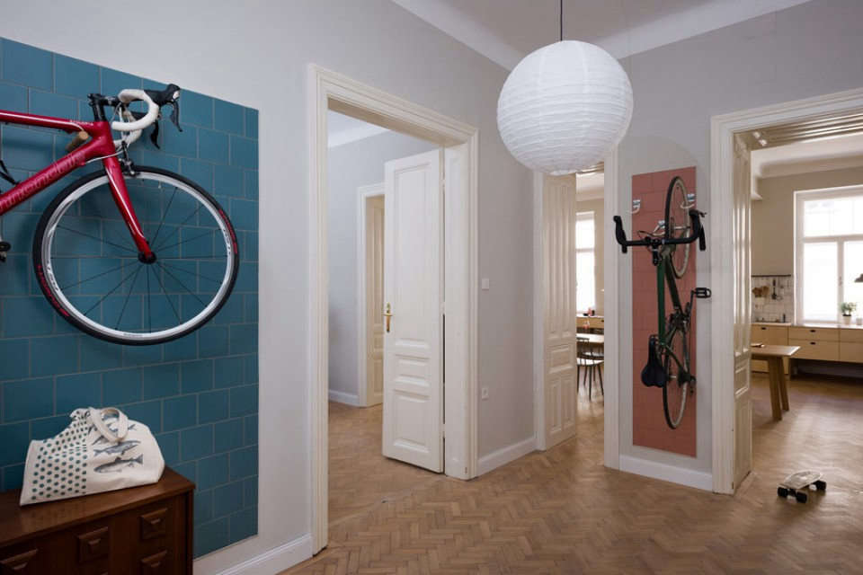 The large entry with dedicated wall storage for bikes. Colored tiles were used to create accent walls throughout the apartment. The tiles are from Dutch company Mosa.