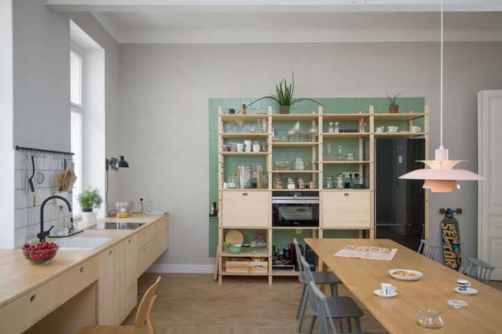 City Slick A Cool Apartment for a Couple Who Lives and Breathes Urban Life A Louis Poulsen PH5 Pendant Lamp hovers over a dining table by Staffan Holm, from Hem. The gray dining chairs are from Hay.