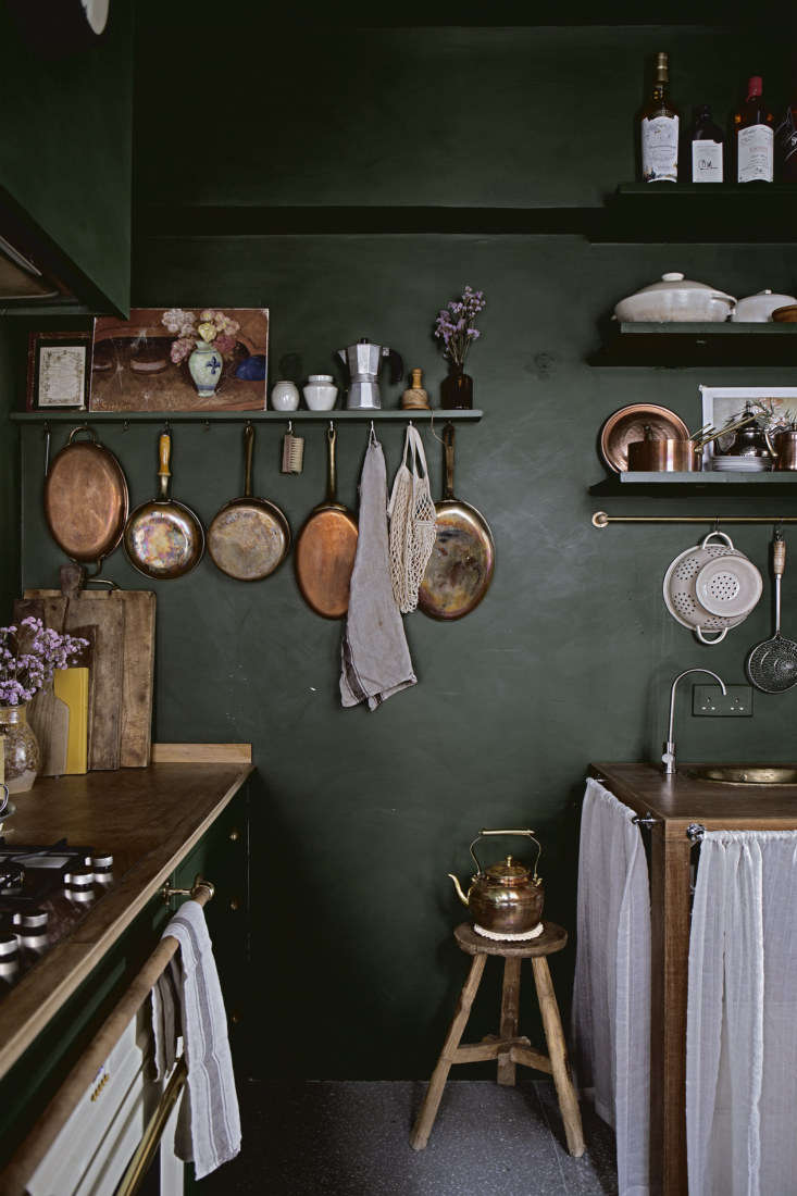 Mandy displays most of her cookware on hooks. Behind the sink skirt are &#8