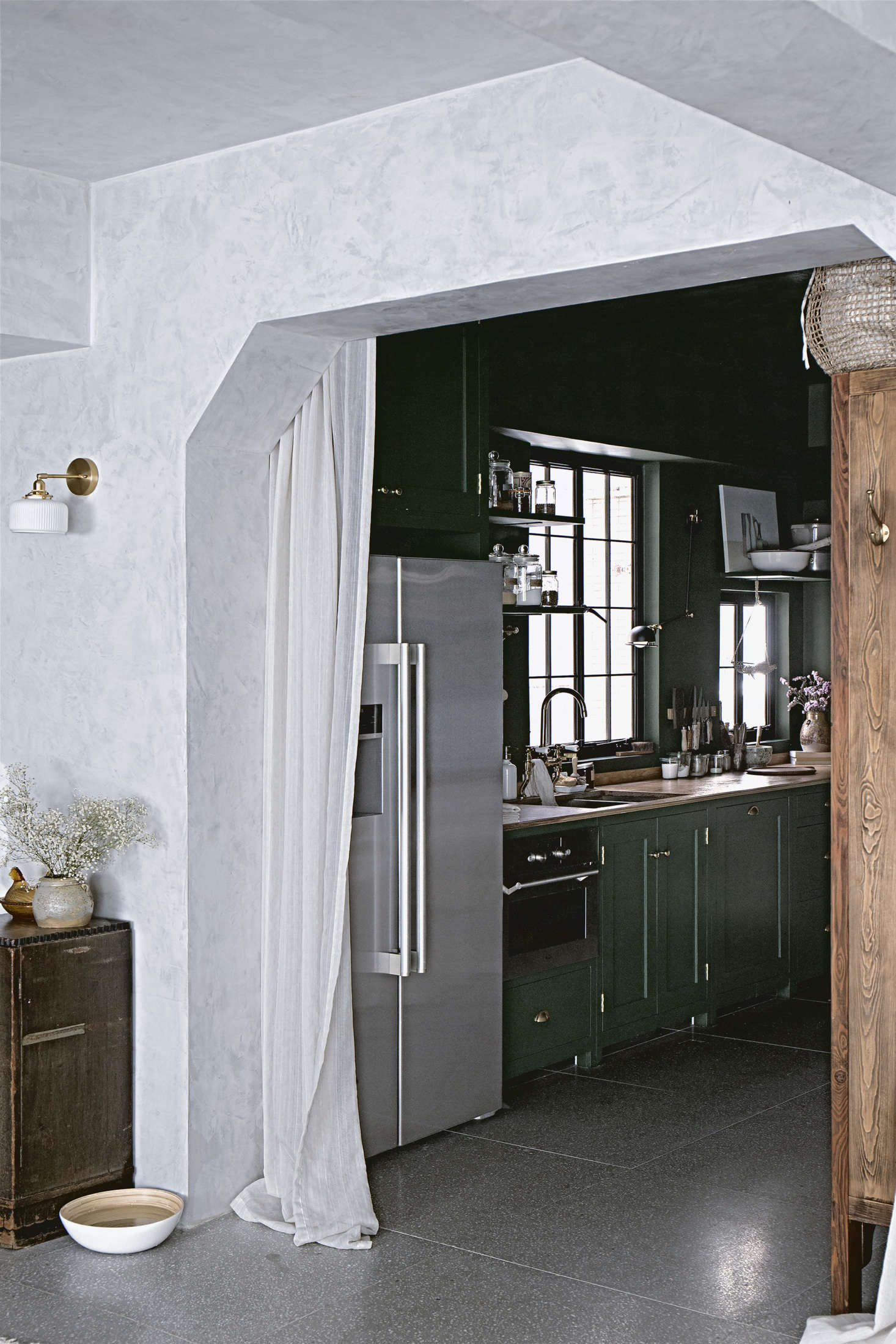 A glimpse of the moody green kitchen. Their dogs' water bowl sits on the tiled palazzo floor. See Kitchen of the Week: The &#8