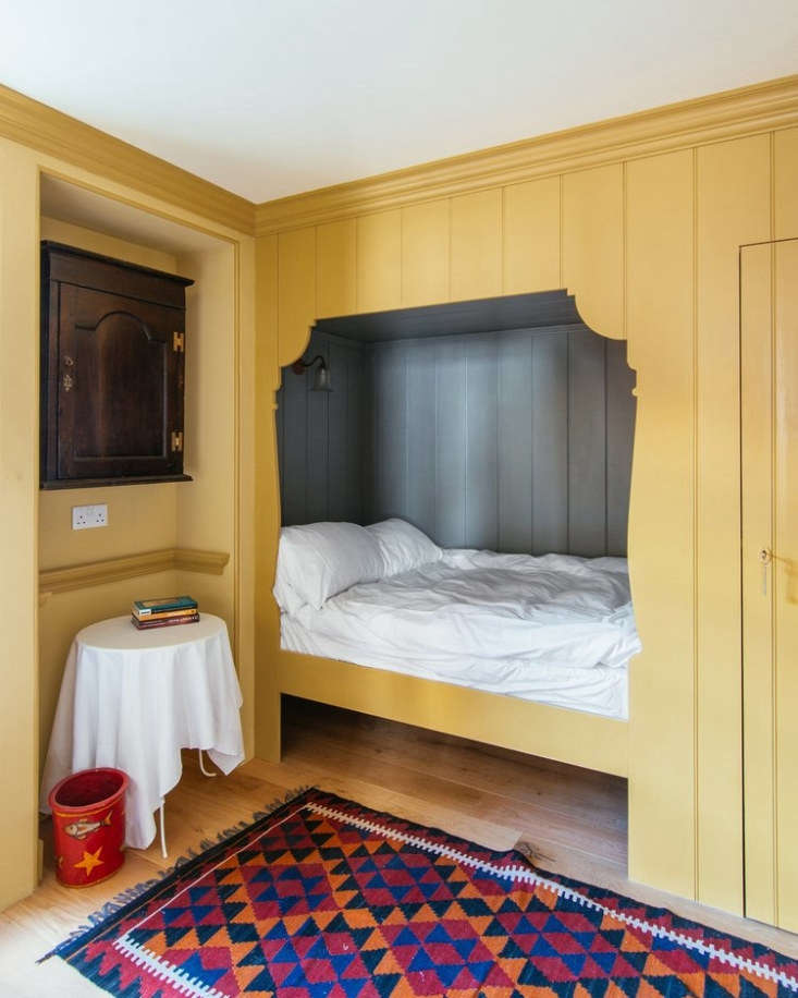 A cozy room on the second floor with an alcove bed painted India Yellow.
