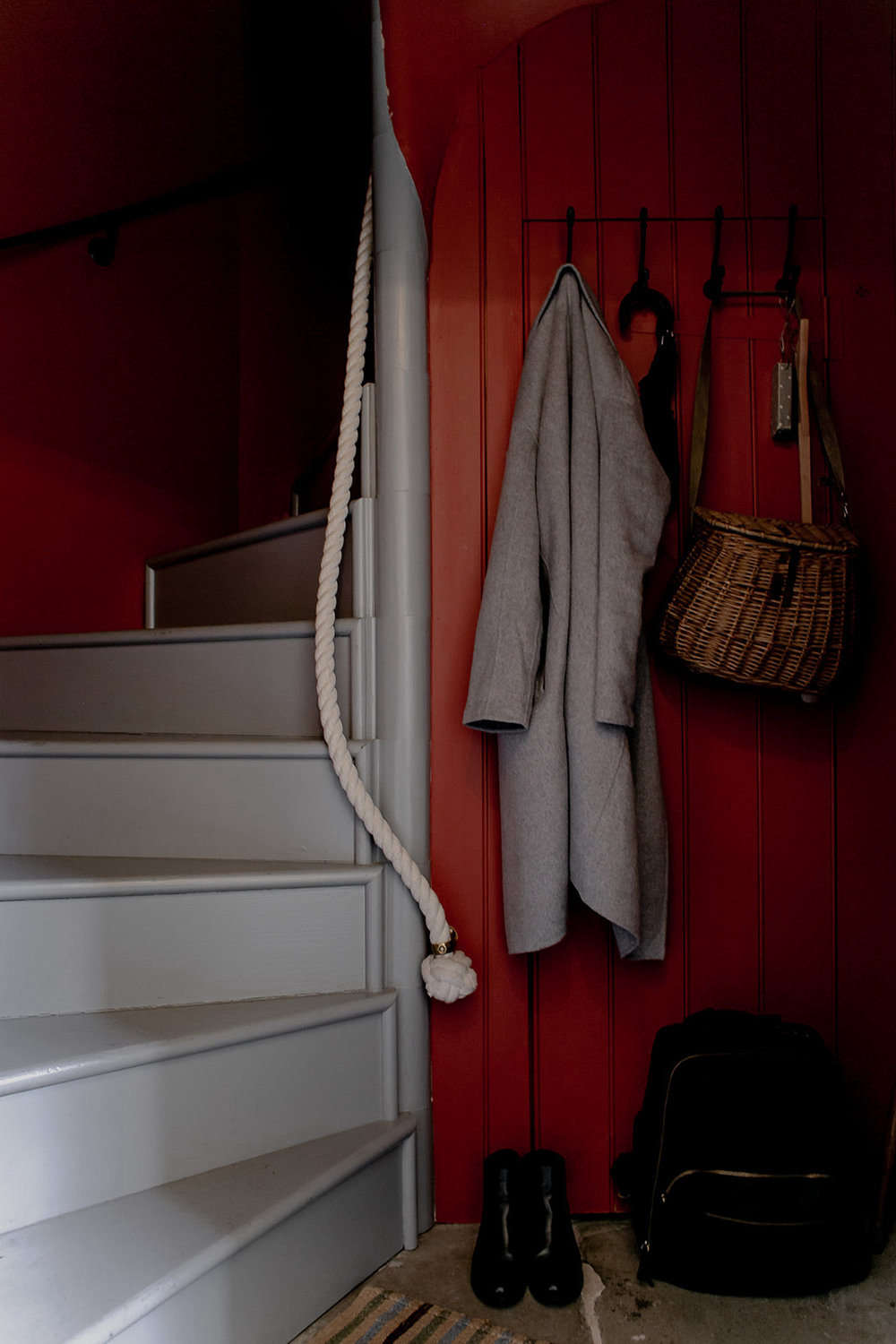 A winding staircase with a rope rail greets guests. The walls here are painted Terre d&#8