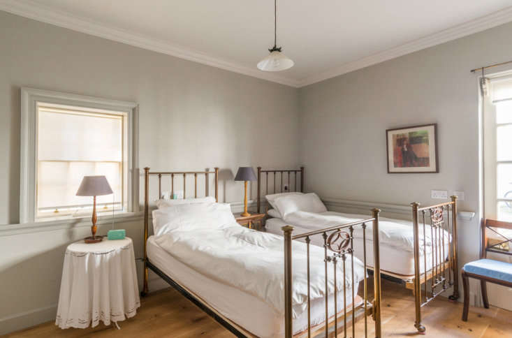 The house has a surprising layout, with the three bedrooms on the lower two floors and the living room and kitchen on the top floor. This guestroom, on the ground floor, features walls painted Pavilion Gray.
