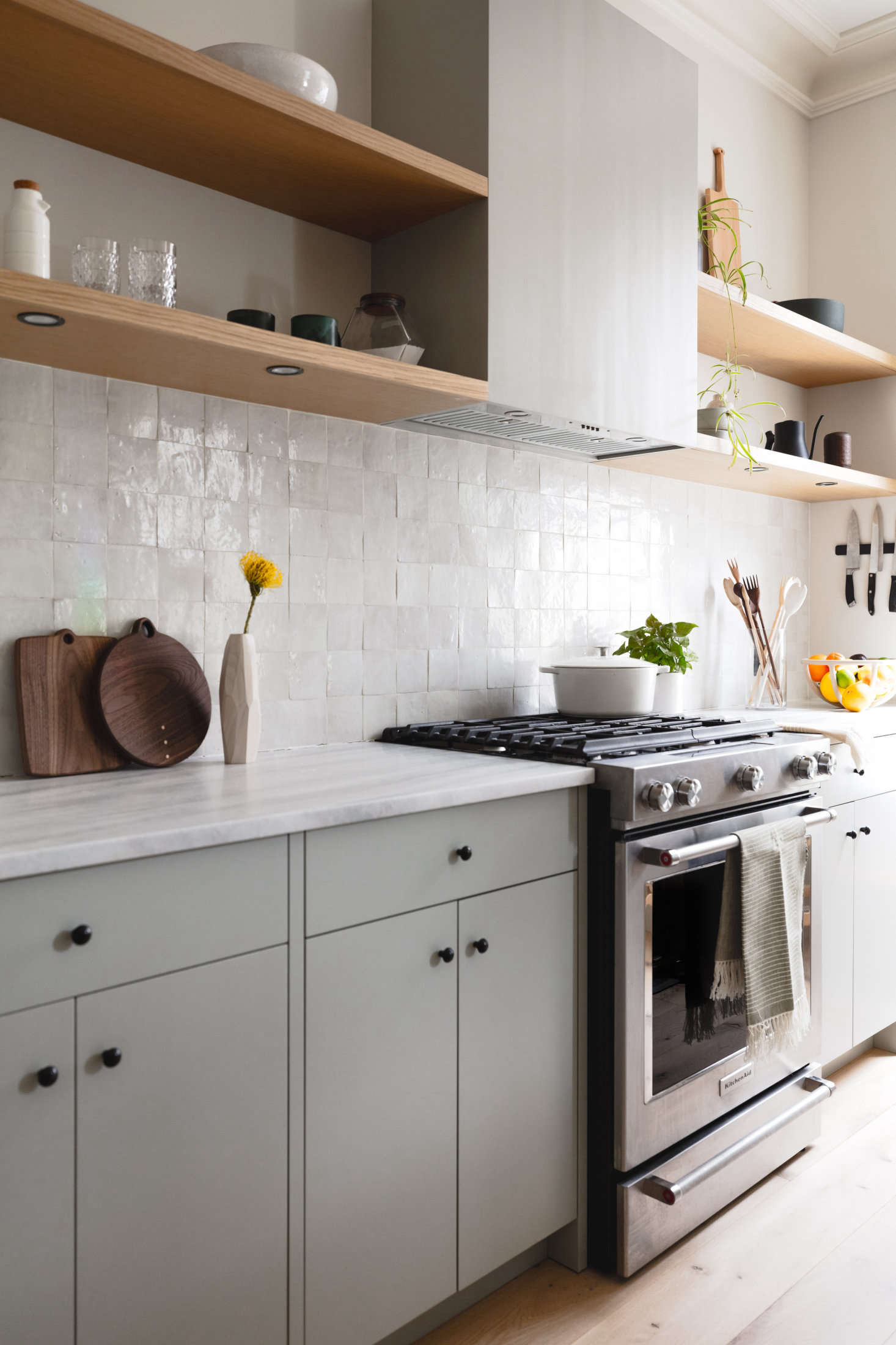 Like the island, the counters are Pentelicus Venato marble. The range is a KitchenAid. Note the gracefully incorporated ventilation hood and under-the-shelf puck lighting—&#8