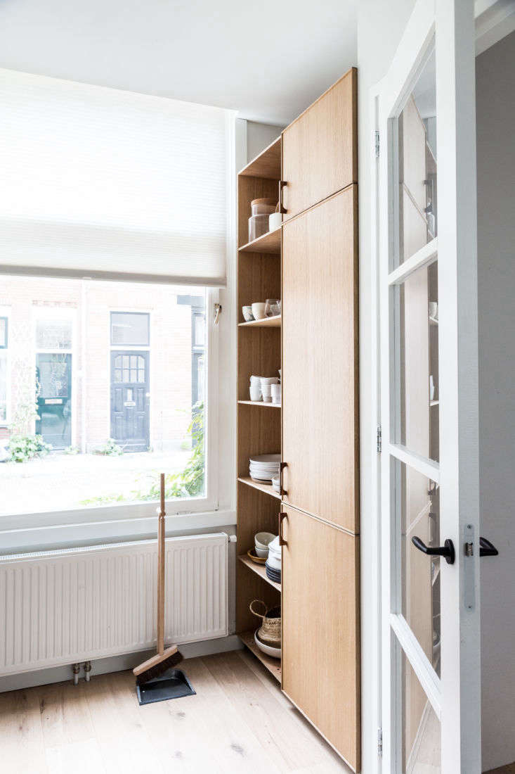 The shifted layout allowed for a nook behind the door, fitted with nearly ceiling-high shelves and cabinets.