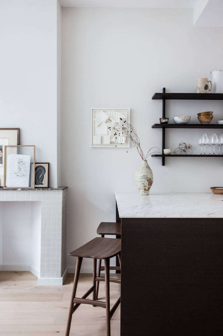 At the other end of the kitchen, the L-shaped counter ends in a peninsula that divides the cooking space from the rest of the downstairs. The mantel was existing, &#8