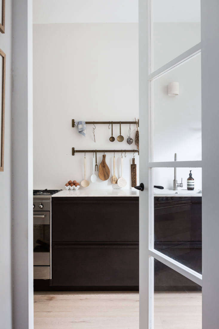 By shifting the entry and stairs just slightly, Holly and Dirk were able to accommodate a longer, brighter kitchen. A glass-paneled door leads to the new space, fitted with a bamboo kitchen by Norwegian sustainable kitchen makers Ask og Eng.