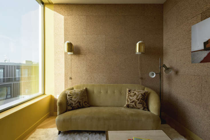 A small, cork-lined room off the kitchen serves as a sitting room/study; the three-seater sofa is upholstered in mustard corduroy.