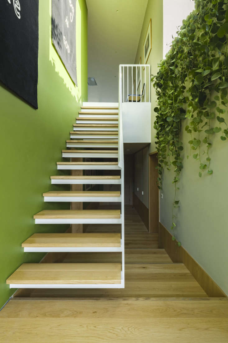 A floating staircase leads to the lower bedroom level.