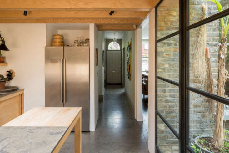 Limestone tiles extend from the entrance, down the hallway, and into the kitchen. The rest of the house enjoys oiled-oak floorboards.