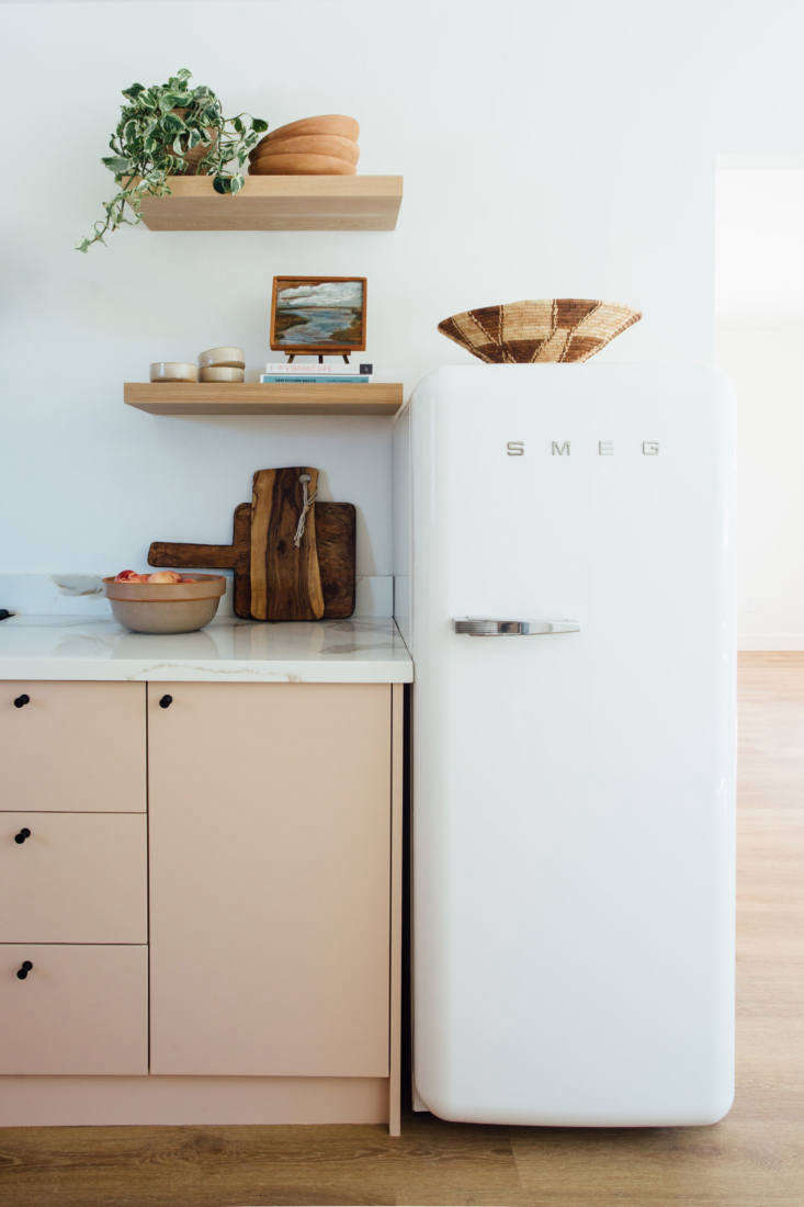 The splurge: a fifties-style Smeg fridge, approximately 57.5-by--inches. The black metal cabinet knobs are Rejuvenation&#8