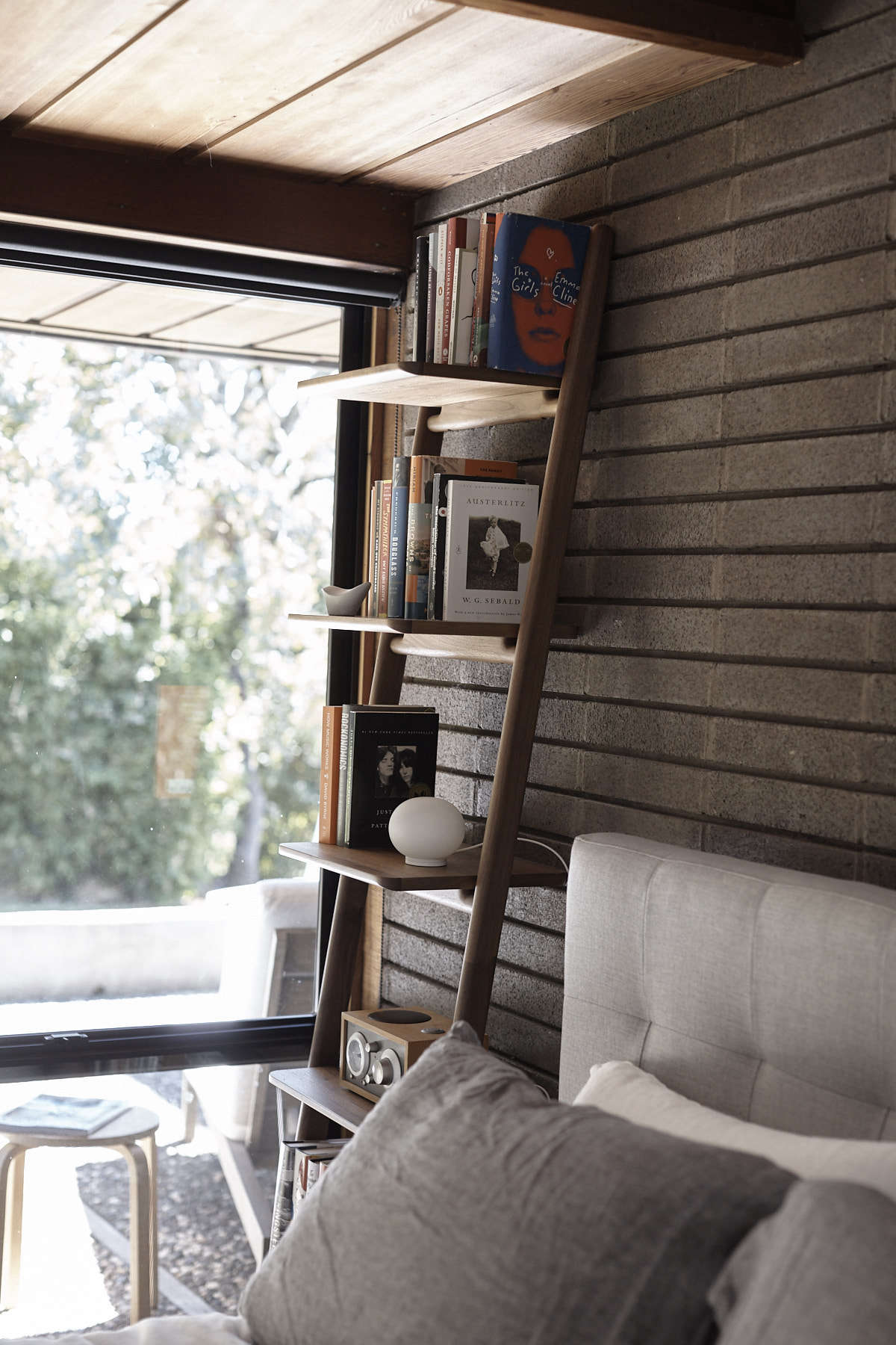 In the master bedroom, the Grid-Tufted Headboard is from West Elm and the Orkney Linen Bedding is from Rough Linen. The walnut Folk Ladder Shelf is by Norm Architects for DWR.