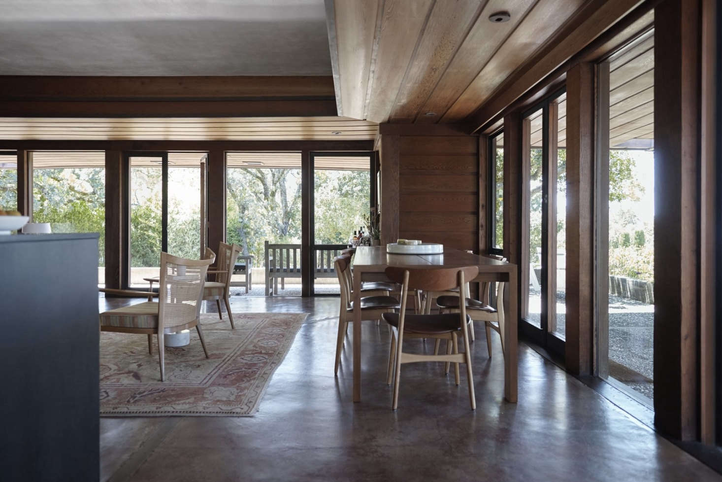 A Henrybuilt walnut dining table is surrounded by iconic original Hans Wegner CH30 chairs. The living room carpet has traveled with Mark and Janet from Seattle to London to San Francisco and now, to Napa.