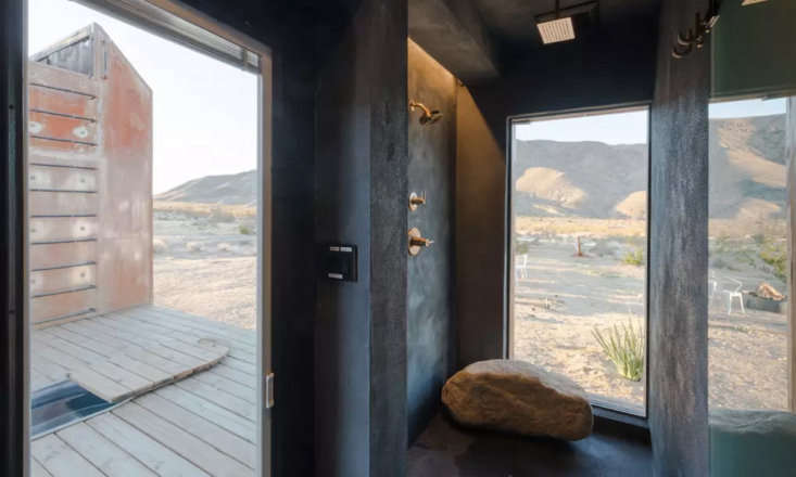 An indoor shower that feels like an outdoor one thanks to boulders and an expansive window.
