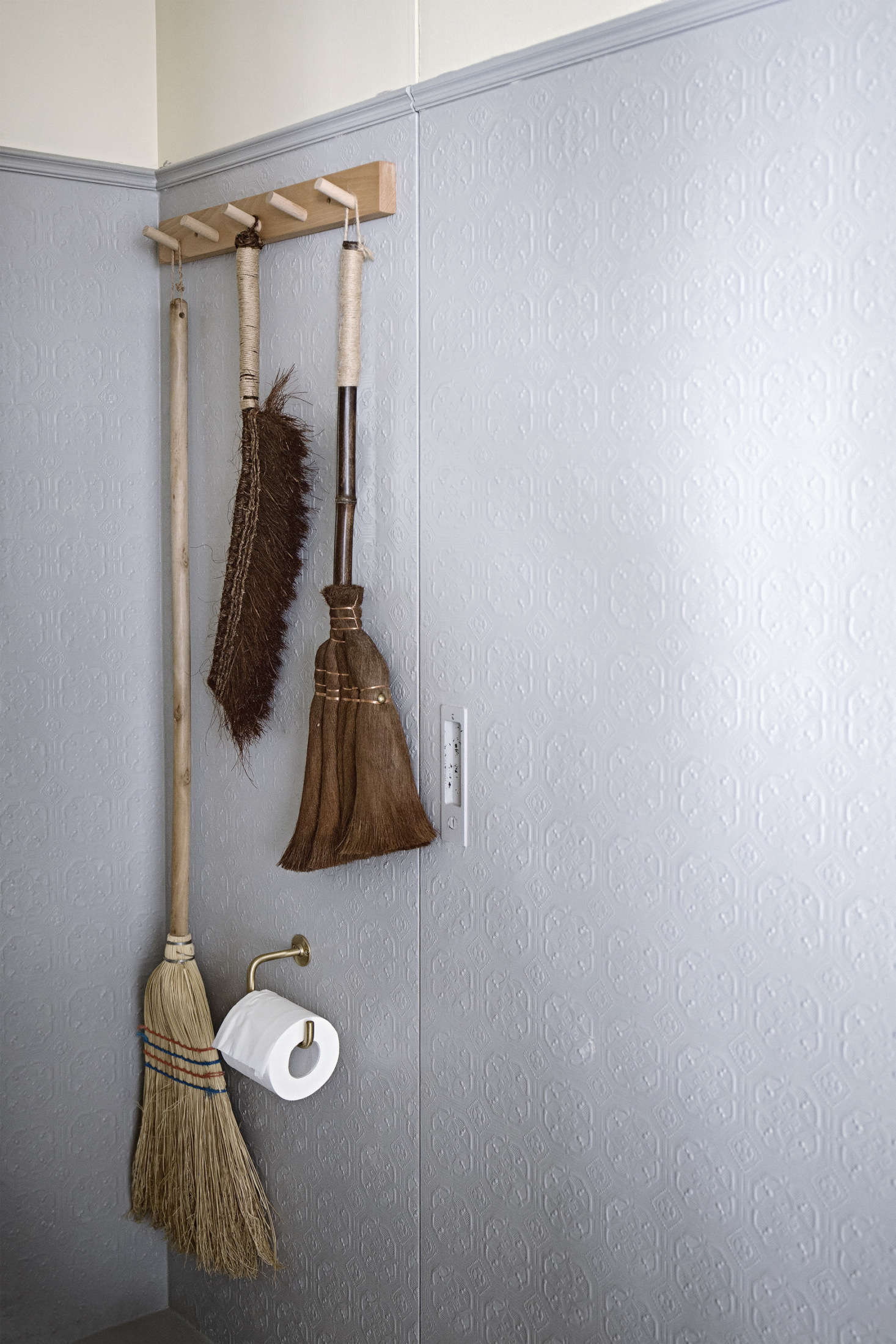 The guest bathroom has artful brooms hanging off a peg rail. Painted textured wallpaper lines the walls here. Mandy&#8