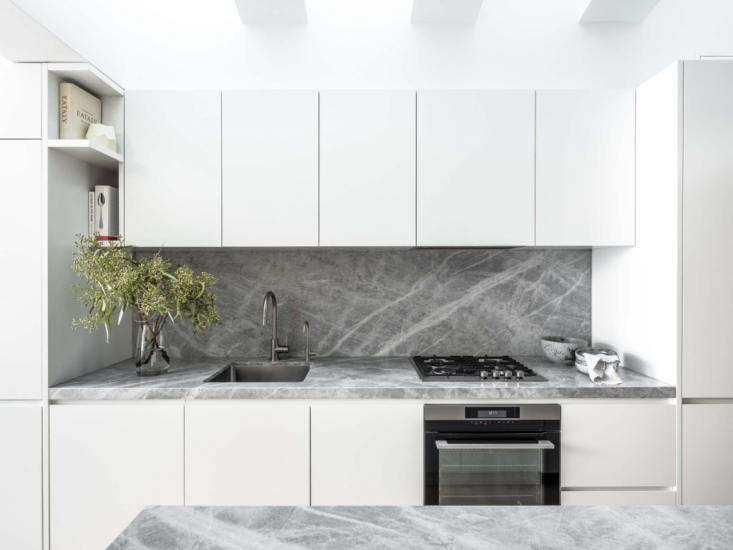 savoy light marble was used for both the counters and blacksplash for uniformit 16