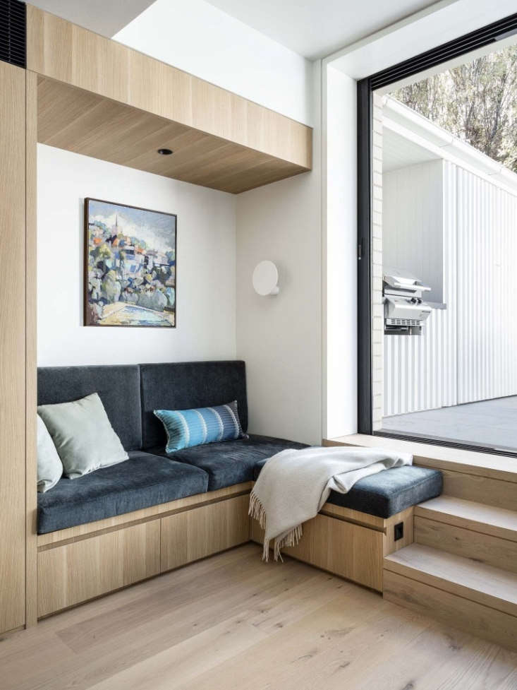 a painting by rocco fazzari hangs above the reading nook. the built in drawers  19